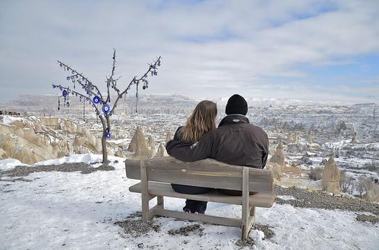 ベンチに座って丘から雪景色を眺めるカップル