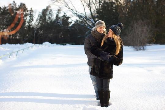 雪景色の中で後ろから女性をハグするカップル