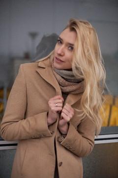 寒そうにキャメルのコートの衿を合わせる女性