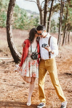 カメラを片手に自然の中を歩くカップル