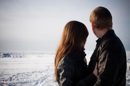 雪の中抱き合い地平線を見つめるカップル