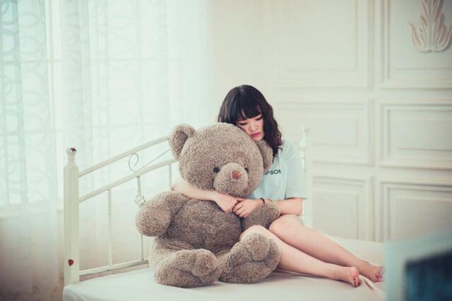理想の恋人を思い描きながらベッドに座り大きなクマのぬいぐるみを抱きしめる女性