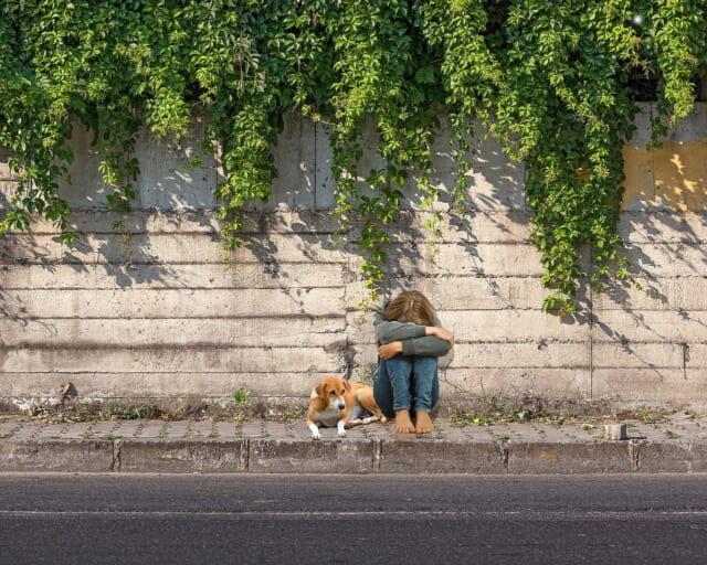 どうせ自分なんか…と犬と一緒に道端にうずくまる女性