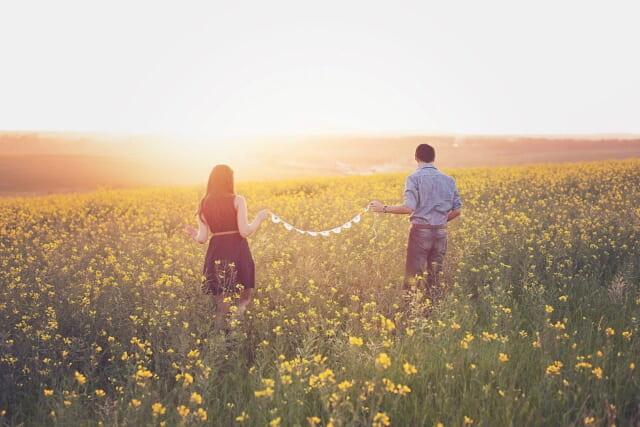 日が傾く中黄色の菜の花畑を幸せそうに歩くカップル