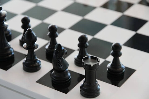 白黒がはっきりしているチェス盤と並んだ黒いチェスピース