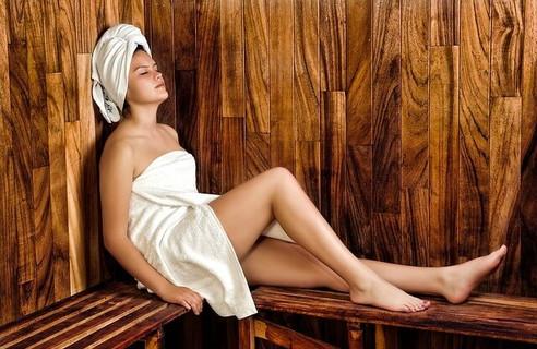 サウナで目を閉じてくつろぐ白いバスタオルを巻いた美容の為には時間を惜しまない女性
