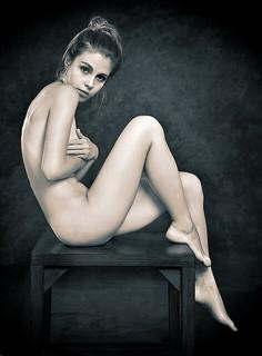 裸で椅子に座る体のガードが硬い女性