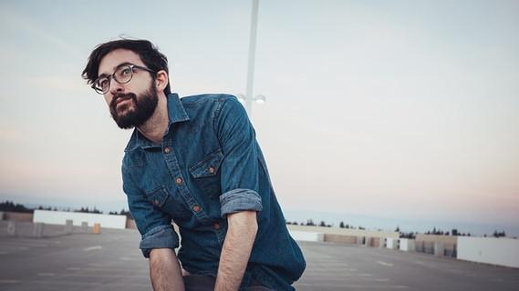 自分が何が好きで何が似合うか知っているインディゴブルーのデニムシャツにひげとメガネが印象的な男性