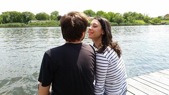 川辺に座り見つめ合い過去の恋愛について話し合うカップル
