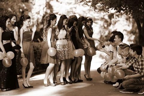 笑顔できさくに話すドレスを着た風船を持った女の子たちとその前でひざまづく男の子たち