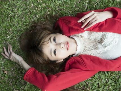 草むらに寝転がる白いブラウスに赤いスウェットを着た非モテを脱出しようと心に決めた女性