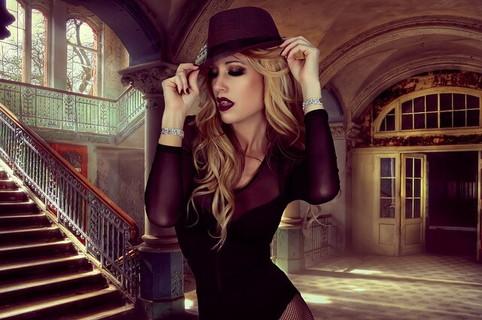 豪邸のエントランスに立つ黒いボディズーツを着て帽子を被った個性的なファッションの女性