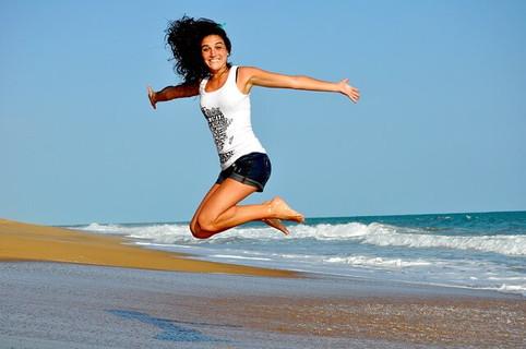 海辺でジャンプするいつも明るく元気いっぱいの女性
