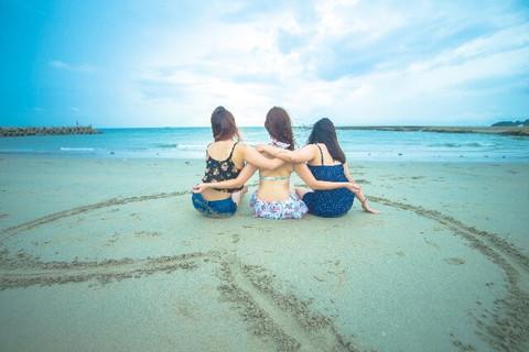 砂浜に描かれたハートの中に座る水着姿の仲良し女の子3人組
