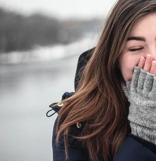 寒い季節でも心は暖か、雪景色の中で口に手を当てて微笑む女性