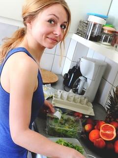 キッチンに立ちまな板の上に葉野菜を乗せる料理上手な女性