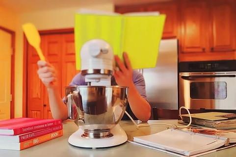 片手にゴムベラを持ち、キッチンのテーブルに肘を付きながら料理本を眺める料理に初挑戦の女性