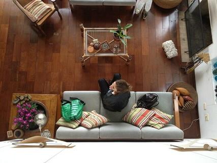 ハイアングルから見たナチュラルなインテリアの居心地の良さそうな部屋とソファに座った女性