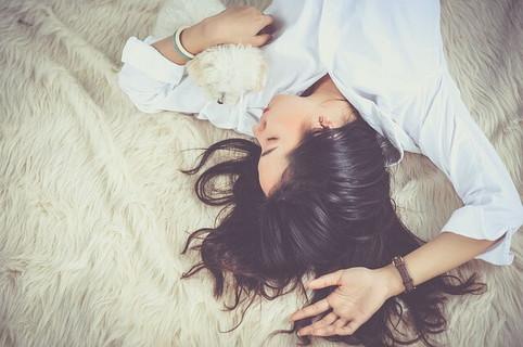 リラックスして寝転がる白いシャツを着て白いじゅうたんの上に寝そべる女性と白いトイプードル