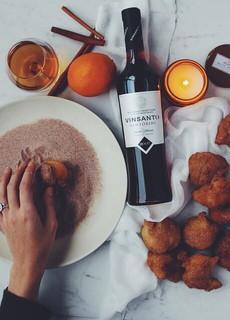 ドーナツにシナモンをまぶす手とキャンドルとワインのボトルが乗ったおうちデートの気分を盛り上げてくれそうなテーブル