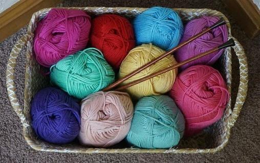 四角いカゴに入った色とりどりのあたたかそうな毛糸と編み針