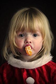サンタの衣装を着てみかんを口にくわえる女の子