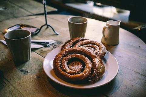 丸い木のテーブルの上に乗ったお皿に乗ったパンとおそろいのシンプルなベージュのカップ