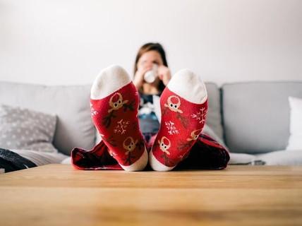 家に引きこもり赤いトナカイ柄のくつしたを履いた足をテーブルの上に乗せソファに座る女性