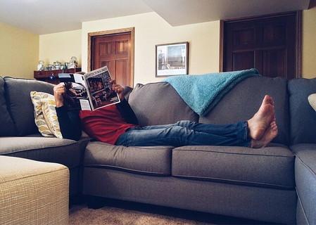 ソファに寝そべりだらだらと雑誌を読む男性