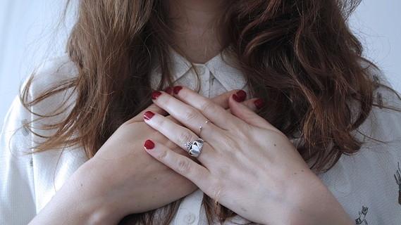 胸に両手を当て運命の瞬間を感じる白いブラウスにロングヘアの女性