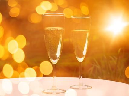 出会いを予感させるテーブルの上に乗った2つのシャンパングラスとピンボケしたキラキラ輝く光