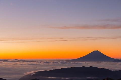 初日の出でオレンジ色に染まった空と富士山のシルエット