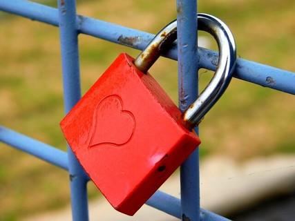 青いフェンスにつけられた運命の出会いを感じさせるハートの印のある赤い南京錠