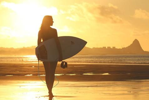 自分みがきに余念がない朝焼けの中サーフボードを持ってあるく女性サーファー