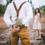 線路の上に立ち笑顔で後ろを振り返る女性と背中に花束を隠し持つ男性