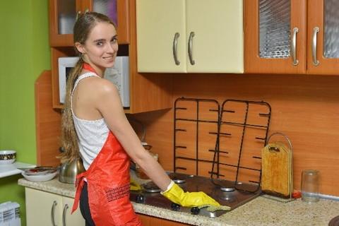 オレンジのエプロンを着けてキッチンの一年の汚れを残さずピカピカ掃除する女性