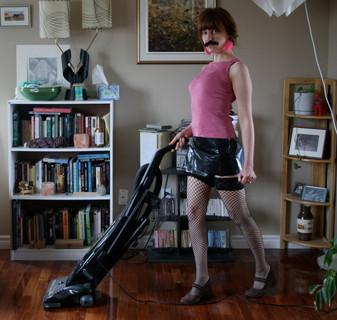 つけヒゲに編みタイツ姿で楽しそうに掃除機をかける女性