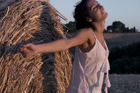 積まれたワラの前で朝日を浴びながら手を広げて気持ち良さそうに深呼吸する女性