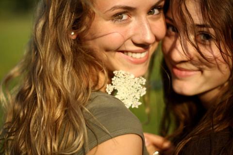 ツヤツヤな肌と健康的な笑顔で振り返るロングヘアの女性2人と白い花