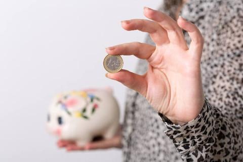 どんどんお金が貯まるブタの貯金箱とコインを持った女性の手元
