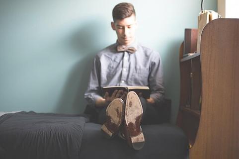 スッキリと片付いた部屋でチョウネクタイをつけて足を伸ばしながらベッドに座り本を読む男性