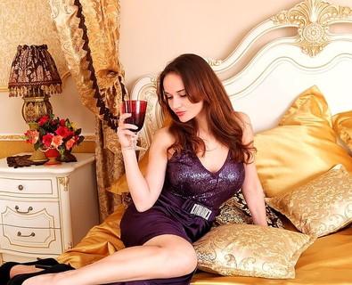 紫色のドレスを着てゴールド系でまとめられたベッドの上に座るワイングラスを持ったイイ女
