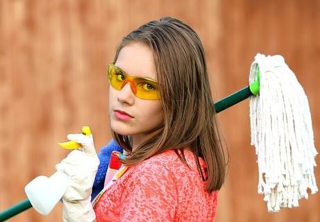 モップとスプレーを持ちゴーグルをかけたお掃除体制万全の女性