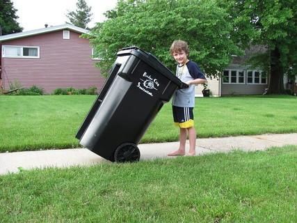 ゴミがたくさん入った黒い大きなゴミ箱を運ぶ男の子