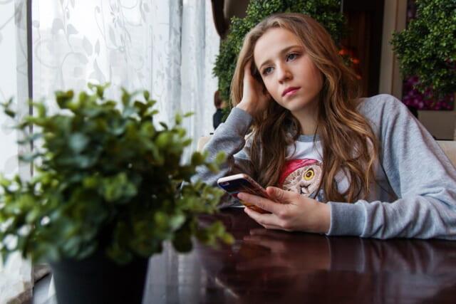 思案顔でテーブルに肘を付き携帯を持って返事を待つ女性