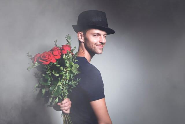 マンネリ化対策に彼女へのサプライズにバラの花束を用意して微笑む男性