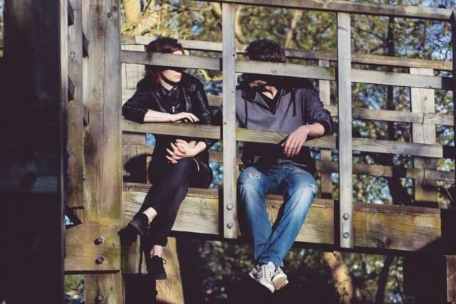 2人の関係がマンネリ化しないよう橋の上に腰掛け話し合うカップル