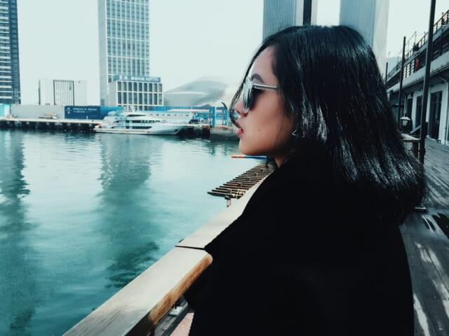 たまにはひとりの時間もいいものだなと海を見てたそがれるサングラスをかけた女性