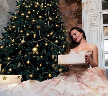 大きなクリスマスツリーの前で大きなプレゼントを持ちピンク色のドレスを着て座る女性