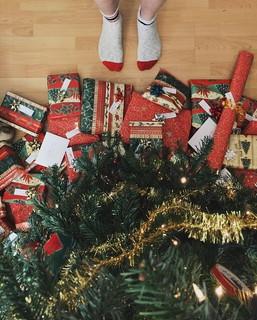 クリスマスツリーの前に立ちたくさんのプレゼントを眺める男の子の足元